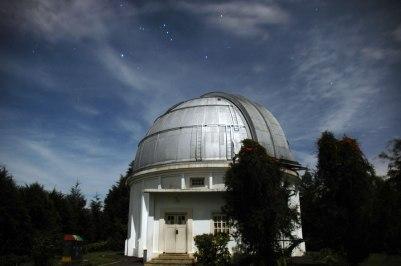 Di atas Kupel atau Kubah teropong zeiss tampak rasi Orion. Orion merupakan rasi bintang yang cukup mudah dikenali. Rasi bintang orion disebut juga rasi bintang pemburu. Di jawa, rasi orion disebut juga rasi waluku yang digunakan sebagai penanda bercocok tanam. Pada foto diatas tampak tiga bintang berjajar dari atas ke bawah agak sedikit miring ke kanan, adalah sabuk orion. Mulai dari bintang paling atas adalah Alnitak, Alnilam, dan Mintaka. Disebelah kanan Alnitak tampak bintang dengan warna kekuning-kuningan dan agak sedikit tertutup awan adalah bintang Betelgeuse. Betelgeuse memiliki diameter sekitar 1.180 kali diameter Matahari. Seandainya Betelgeuse adalah bola yang kosong, maka Betelgeuse bisa muat menampung matahari dengan jumlah 1,6 Milyar lebih. Foto ini diambil tanggal 19 Februari 2011 sekitar jam setengah sebelas malam. Cahaya terang yang menyinari kupel dan sekitar berasal dari cahaya bulan. © Alfan Nasrulloh/Obs. Bosscha